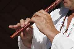 Flute playing. Close-up of man playing the wooden flute Royalty Free Stock Photo