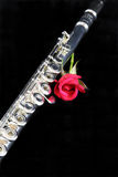 Flute and Red Rose On Black. A professional silver flute with a red rose isolated against a black background in the vertical format with copy space Royalty Free Stock Photos