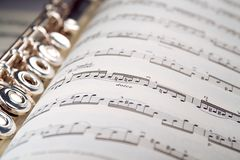 A flute rests inside a musical score. A used flute lies along the spine of an open musical score. Only one line of music is in focus Royalty Free Stock Photos