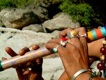 Flute and rings. A man playing a traditional flute wearing colourful rings Stock Images
