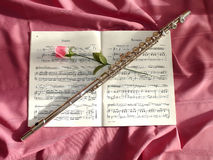 Flute and rose. On a partition Royalty Free Stock Image