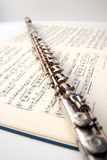 A flute on sheet music Stock Images