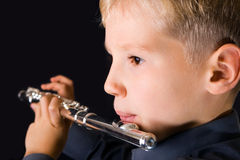 Flute sounds. The ten years' boy playing a flute Stock Image