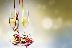 Flutes champagne glasses and colorful streamers against a bokeh royalty free stock photo