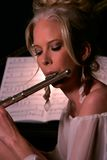 The Flutist. Attractive female flutist playing a flute royalty free stock image