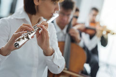 Flutist playing her instrument on stage Stock Images