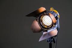 Flutlicht mit Halogen Lampe und Fresnellinse auf einem grauen Hintergrund Lichttechnische Ausrüstung für das Schießen Lizenzfreies Stockfoto