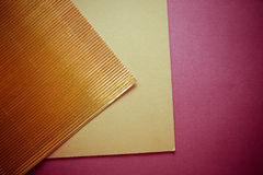 Flutted golden paper on crimson background Stock Images