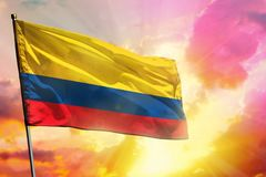 Fluttering Colombia flag on beautiful colorful sunset or sunrise background. Success concept. Fluttering Colombia flag on beautiful colorful sunset or sunrise stock photography