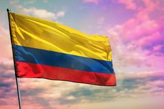 Fluttering Colombia flag on colorful cloudy sky background. Prosperity concept. Fluttering Colombia flag on colorful cloudy sky background. Colombia prospering royalty free stock photos