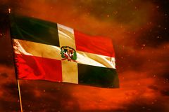 Fluttering Dominican Republic flag on crimson red sky with smoke pillars background. Troubles concept. Fluttering Dominican Republic flag on crimson red sky with royalty free stock photo