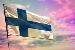 Fluttering Finland flag on colorful cloudy sky background. Prosperity concept. Fluttering Finland flag on colorful cloudy sky background. Finland prospering stock photos