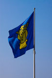 Fluttering flag with the coat of arms of Stockholm. Against the blue sky royalty free stock images