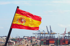 Fluttering flag of Kingdom of Spain and cargo port, Valencia Royalty Free Stock Photo