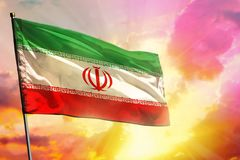 Fluttering Iran flag on beautiful colorful sunset or sunrise background. Success concept. Fluttering Iran flag on beautiful colorful sunset or sunrise background royalty free stock photo
