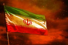 Fluttering Iran flag on crimson red sky with smoke pillars background. Troubles concept. Fluttering Iran flag on crimson red sky with smoke pillars background royalty free stock images