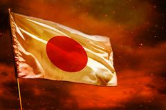 Fluttering Japan flag on crimson red sky with smoke pillars background. Troubles concept. Fluttering Japan flag on crimson red sky with smoke pillars background royalty free stock images