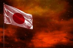 Fluttering Japan flag mockup with blank space for your text on crimson red sky with smoke pillars background. Troubles concept. Fluttering Japan flag mockup stock photo