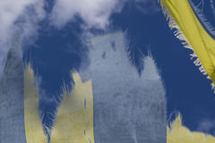 Fluttering in the wind blue and yellow fabric in the sky. Royalty Free Stock Image