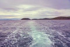 Flutua o barco atrás dele uma pena bonita da água e das bolhas no horizonte que você pode ver a ilha Fotos de Stock Royalty Free