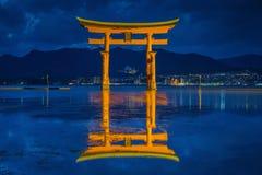 Flutuador gigante da porta do torii na água no crepúsculo imagem de stock royalty free