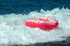 Flutuador polvilhado moderno da filhós em ondas do mar Fundo do verão fotos de stock royalty free