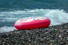 Flutuador polvilhado moderno da filhós em ondas do mar Fundo do verão fotografia de stock