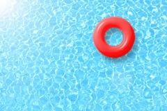 Flutuador vermelho do anel da piscina na água azul e no sol brilhantes