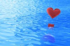 Flutuador vermelho do balão de ar do coração da tela no mar imagem de stock royalty free