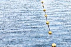 Flutuadores amarelos do flutuador em uma corda que flutua no mar foto de stock