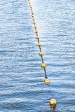 Flutuadores amarelos do flutuador em uma corda que flutua no mar imagem de stock