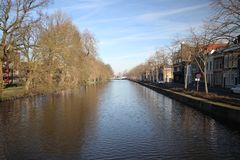 Fluwelensingel with the canal and a weeping willow without leaves in the winter in Gouda, the Netherlands. Fluwelensingel with the canal and a weeping willow stock photo