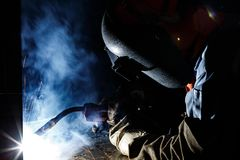 Flux cored wire arc welding process. Worker fabricate structure by flux cored wire arc welding process Royalty Free Stock Image