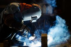 Flux cored wire arc welding process. Worker fabricate structure by flux cored wire arc welding process Stock Image