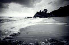 Fluxo branco impressionante preto e branco da onda que bate o Sandy Beach fotografia de stock