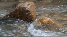 Fluxo da água batido a rocha e a onda que espirram no rio vídeos de arquivo
