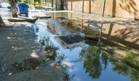 Fluxo da água durante a chuva pesada e obstrução da água de esgoto da rua O fluxo da água durante um furacão forte em esgotos da  imagens de stock