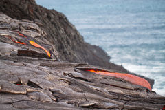 Fluxo da lava encarnado no Oceano Pacífico foto de stock