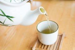 Fluxo do chá de Grean do potenciômetro do chá a um copo branco Imagens de Stock Royalty Free