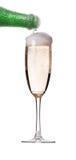 Fluxo do champanhe do frasco no vidro imagem de stock