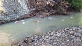 Fluxo do rio que está completo do lixo video estoque