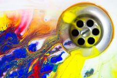 Fluxo multicolorido líquido no dreno de dissipador, conceito da pintura da faculdade criadora Imagens de Stock Royalty Free