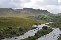 Fluxo pequeno do rio na paisagem verde da vegetação e da montanha em uma estrada nacional na Irlanda Imagens de Stock