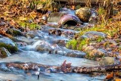 Fluxos da água da inundação através de uma tubulação intersting e de uns ramos tragados cercados pela folhagem de outono colorida foto de stock