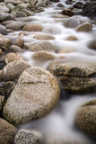 Fluxos de córrego sobre rochas vestidas água Imagens de Stock Royalty Free