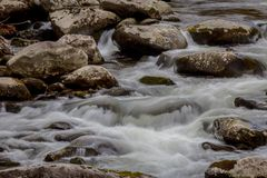 Fluya con tactos de las reflexiones azules, hojas de la caída, agua que fluye sobre rocas imagenes de archivo