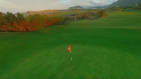 Fly around the golf pin on the sunset background stock video footage