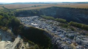 Fly around rubbish dump near weat agricultural fields. Aerial view. Autumn morning stock video
