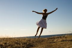 Fly away. Pretty blond jumping Stock Images
