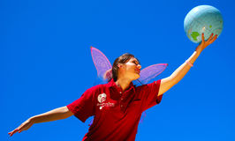 Fly away with Dreamstime. Caucasian white young woman with butterfly wings wearing the Cranberry Dreamstime Polo Shirt, holding a globe in her hand and dreaming Royalty Free Stock Photography